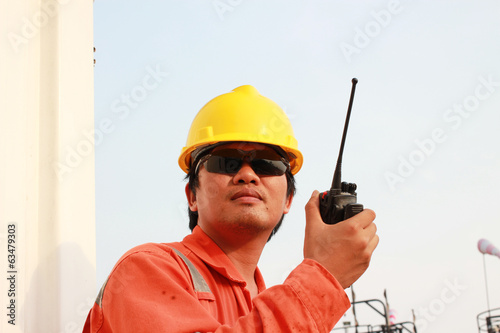 Man in hard hat using walkie talkie