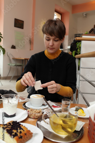 Woman pouring sugar into cup of coffee