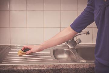 Woman cleaning around the kitchen sink
