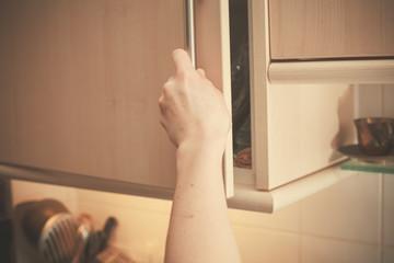 Hand opening kitchen cupboard