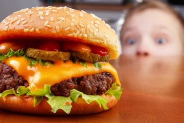 Hungry young boy is staring and smelling a burger