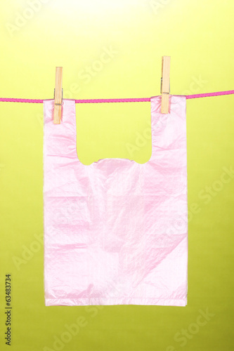 Cellophane bag hanging on rope on green background