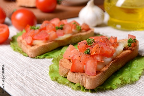 Delicious bruschetta with tomatoes on table close-up