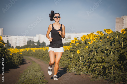 Young lady running on a rural road in sunflower's field