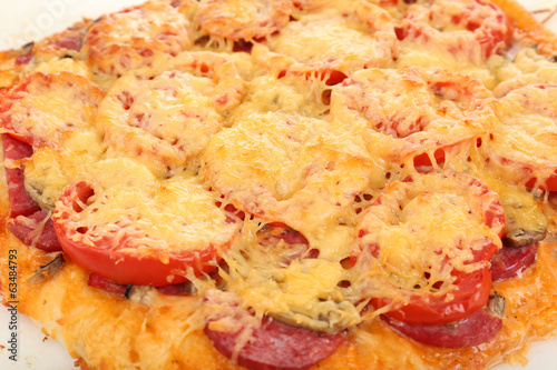 Homemade pizza on baking paper close up