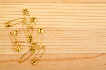 Safety pins on wooden background