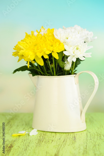 Beautiful chrysanthemum flowers in pitcher on natural