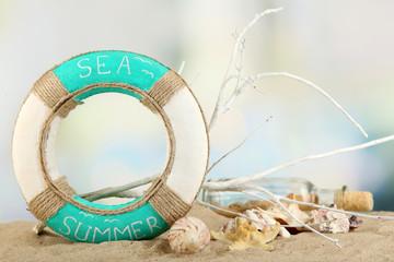 Lifebuoy and sea shells on sand, on light background
