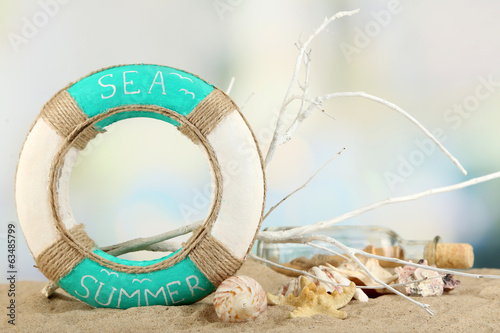 Lifebuoy and sea shells on sand, on light background