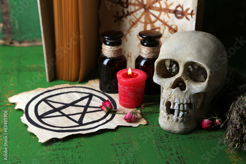 Composition with skull,old book, magic potions, candle and dry