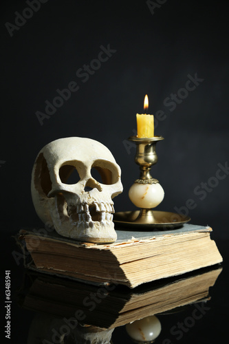 Skull and candle on old book  on dark color background