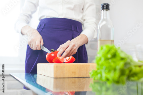Woman makes a salad with olive oil, tomato and salad