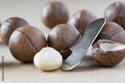 Macadamia nuts with opener, close-up.