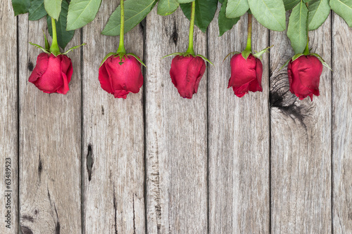 Five red roses on wooden background, top view