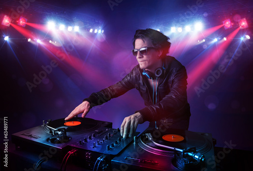 Teenager dj mixing records in front of a crowd on stage