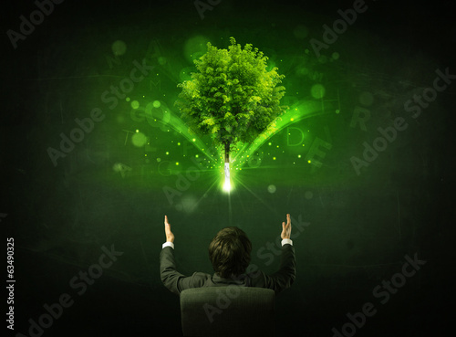 Businessman in chair sitting in front of a glowing tree