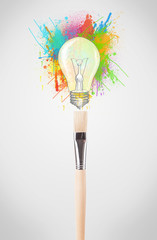 Brush close-up with colored paint splashes and lightbulb