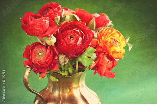 red ranunculus flowers in a metal jug on a green background .