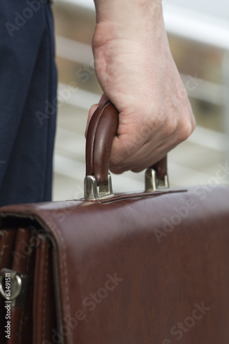 Businessman bears a suitcase