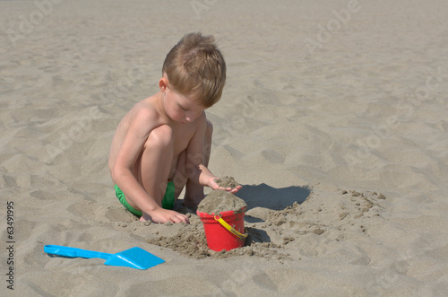 little boy playing with sand