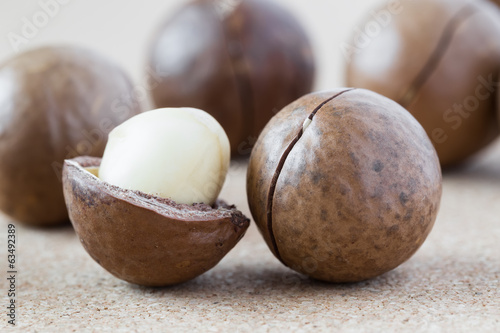 Macadamia nuts on brown background, close-up.