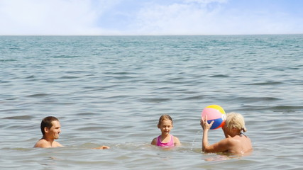 family plays with a ball on the sea