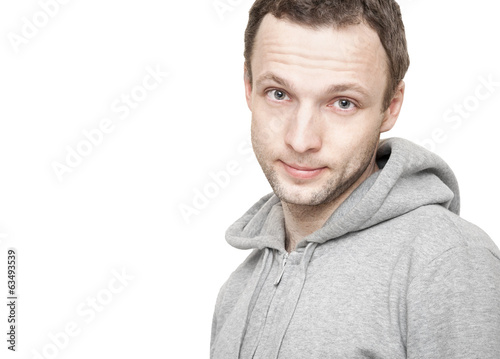 Young Caucasian man in gray sports jacket with hood. Studio port