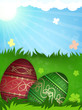 Red and green Easter eggs in grass