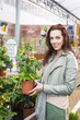 Woman in gardening center shopping for indoor plants