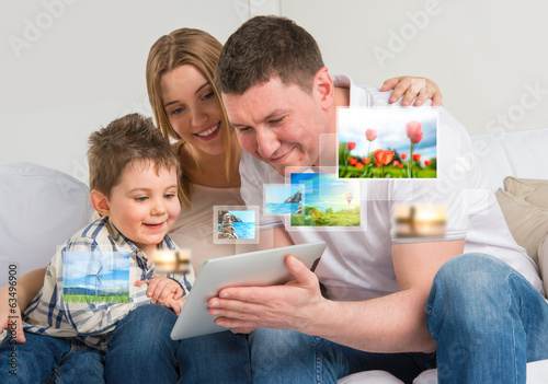Young happy family watching their photo and video files using mo