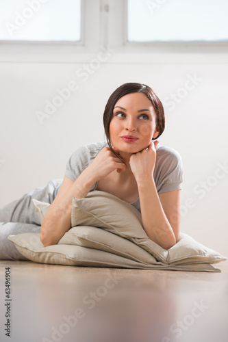 Happy Young Woman Lying On The Floor With Pillows