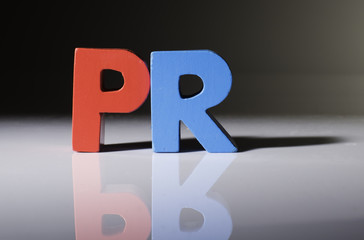 Multicolored word PR made of wood.