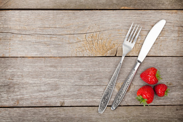 Ripe strawberries with silverware over wooden table background