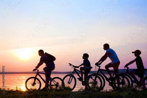 Papiers peints Cyclisme family on bicycles admiring the sunset on the lake. silhouette