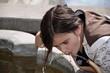 canvas print picture - Mädchen trinkt am Brunnen