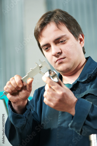 worker measuring detail with caliper