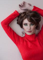 Красивая шатенка со стильным макияжем позирует у белой стены