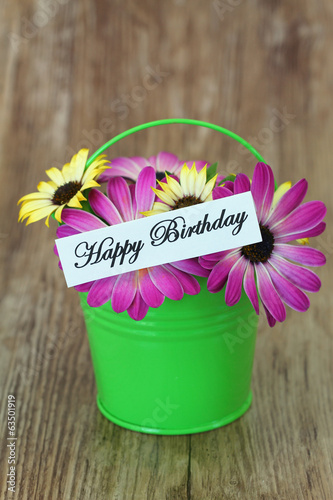 Happy Birthday card with pink and yellow daisies in green bucket