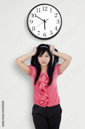 Confused businesswoman under a clock