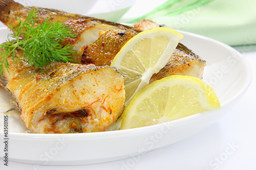 Fried fish with lemon on plate