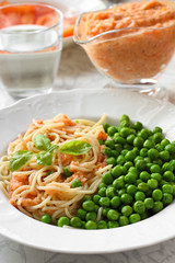 Healthy Vegan meal. Pasta with tomato sauce and green peas