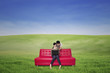 Couple on red sofa using laptop outdoor