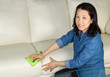Mature woman cleaning Sofa with Microfiber Rag