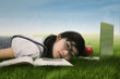 Cute student sleeping on the grass