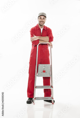 Full length portrait of an handyman in dungarees with a ladder