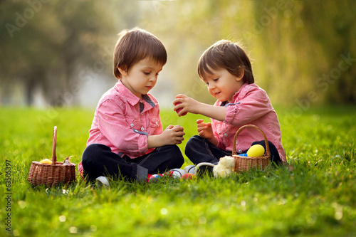 Two boys in the park, having fun with colored eggs for Easter