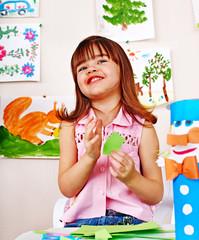 child cutting paper by scissors.