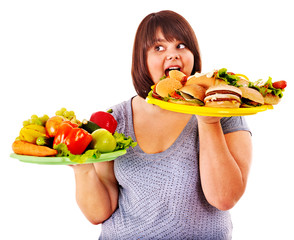 Woman choosing between fruit and hamburger.