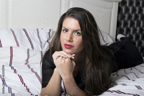 Beautiful woman lying on a bed daydreaming (portrait)