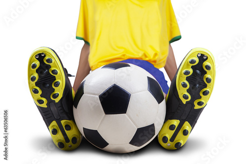Football player sitting with ball isolated